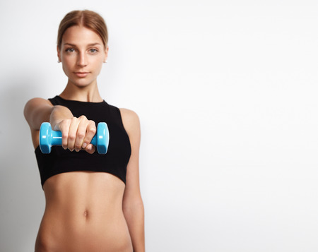 woman holding a barbell towards the camera with a space on a background