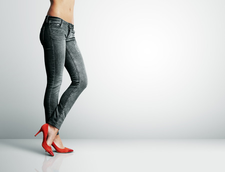 woman in black jeans standing in grey room Stockfoto