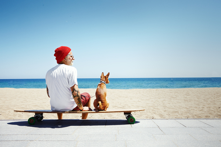 tattooed: man looking like a Santa sitting on the beach Stock Photo