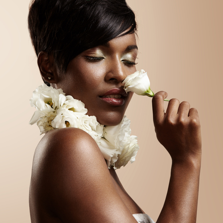 black woman with ideal skin and closed eyes sniffing a flower