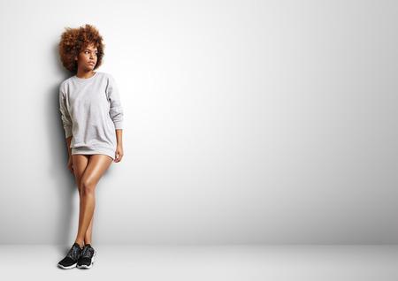 schwarze Frau mit dem lockigen Haar Wearng Sweatshirt wie ein Kleid Standard-Bild