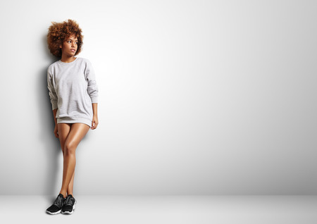 black woman with curly hair wearng sweatshirt like a dress Stockfoto