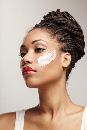 schoonheid zwarte vrouw met een crème op haar wang Stockfoto