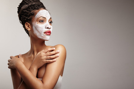 spa treatment: beauty black woman with a facial mask Stock Photo