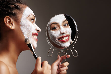 hand mirror: woman applaying mask and watching at camera through the mirror Stock Photo