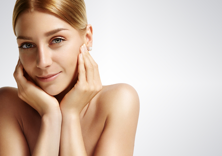 ideal: close-up of a beauty woman with ideal skin looking at camera on a grey background Stock Photo