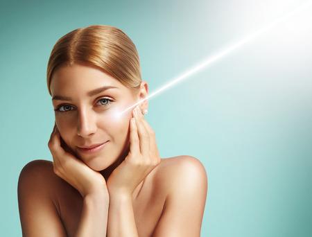 Nahaufnahme Porträt einer Frau, die mit einem Laser auf die Wange Standard-Bild