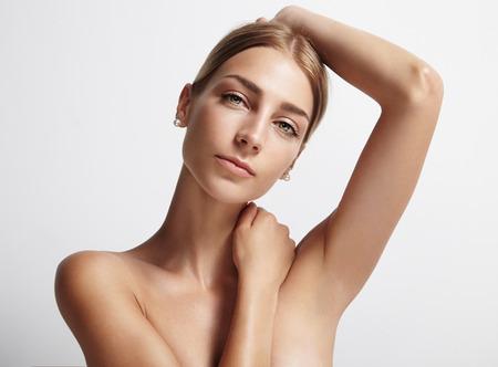 Frau, die ihre Achselhöhle und Blick in die Kamera