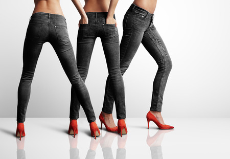 red jeans: three woman in black jeans standing in the grey room Stock Photo