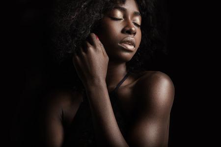seins nus: femme noire sur un fond noir.