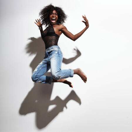 woman screaming: jumping and screaming black an wearing jeans