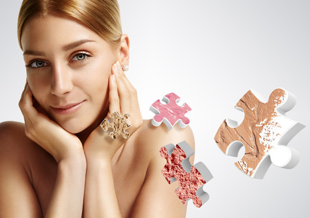 close-up of a beauty woman with ideal skin and puzzle with a different makeup products photo