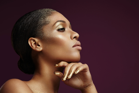 portrait of a black woman with a golden makeup photo