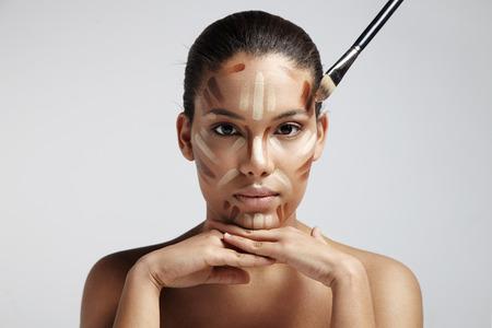 Gesichtskonturen. Frau mit verschiedenen Schattierungen von Fundament, auf ihrem Gesicht Standard-Bild