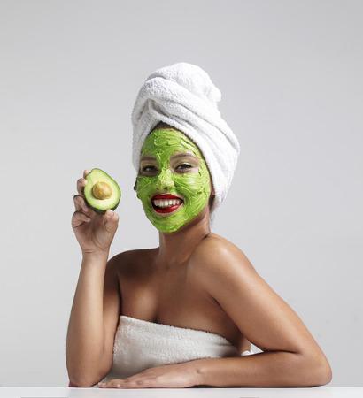 limpieza de cutis: mujer bonita con una m�scara facial de aguacate Foto de archivo
