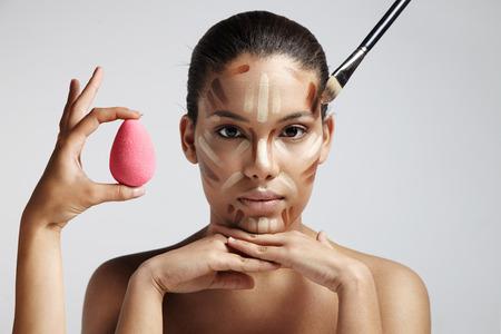mujer maquillandose: Resaltando y el �rea de sombreado que muestra para el contorno de forma de la cara correctiva. contorno facial Foto de archivo