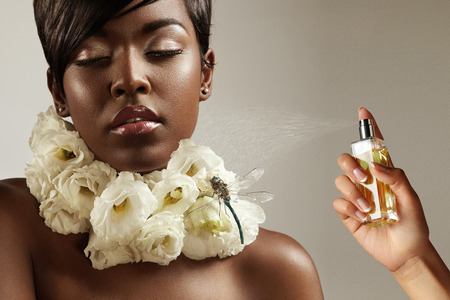 nude nature: beauty black woman with flowers on her neck and a hand with a perfume bottle