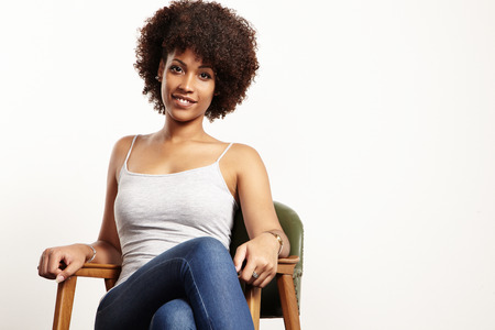 curly: black woman with afra sitting in na chair Stock Photo