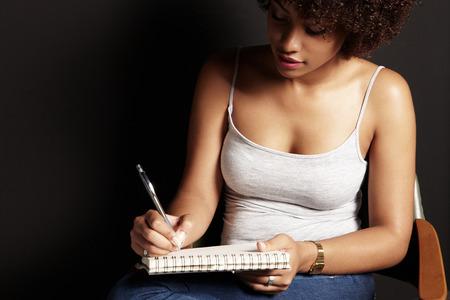 Afrikaanse vrouw schrijft in een donkere kamer