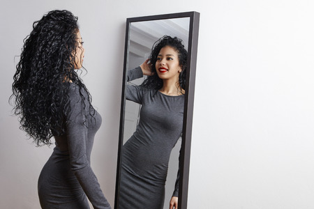 pretty happy woman watching on herself in a big mirror Stockfoto