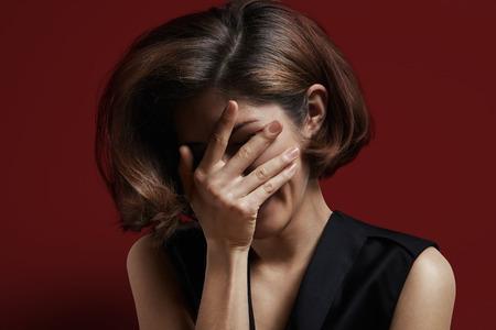 vrouw met een perfecte glanzende haren bedekken haar gezicht met een hand