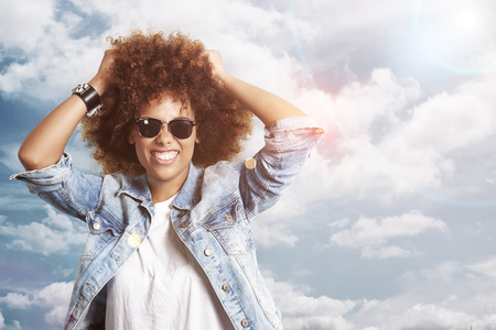 leans: happy woman with a afro hair on a sky background