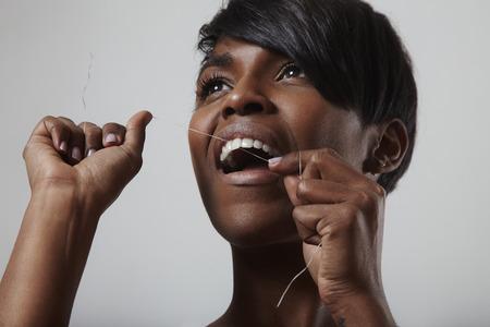 Jong vrouwen glimlachend meisje dat haar witte tanden met tandzijde schoonmaakt Stockfoto