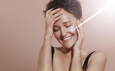 glücklich lächelnde Frau mit Strahl des Lasers auf ihrem ideal Haut