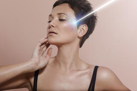 jonge vrouw met een ideale huid en de straal van de laser op het Stockfoto