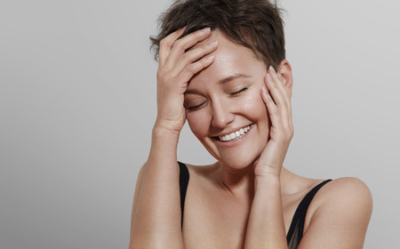 happy laughing girl on a grey background