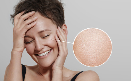 limpieza de cutis: mujer feliz con una lente que muestra su ideal de la piel Foto de archivo