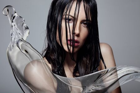 beautycare: woman with a wet hair and water splash
