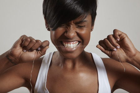 gnaw: woman trying to gnaw through a dental floss