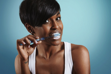 woman cleaning her teeth on blue background