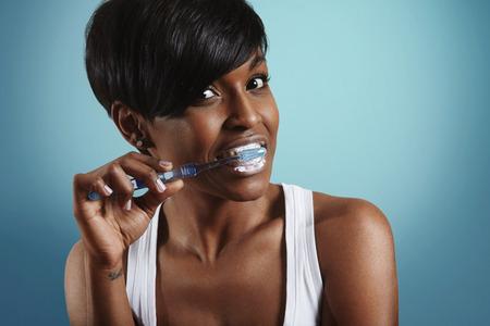 Vrouw reiniging haar tanden op een blauwe achtergrond Stockfoto - 39567966
