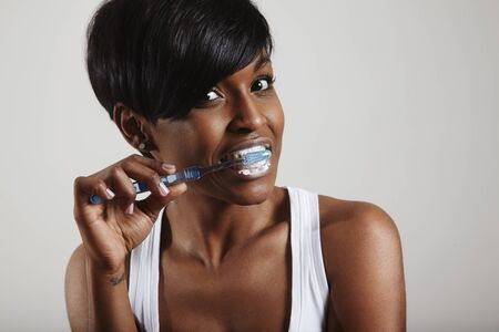 tooth whitening: woman cleaning her teeth Stock Photo