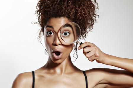 afgevraagd vrouw met een een oog wathing in vergrootglas Stockfoto