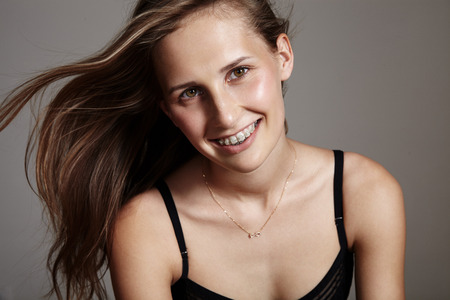 impacted: smiling woman with a blowing hair and braces Stock Photo