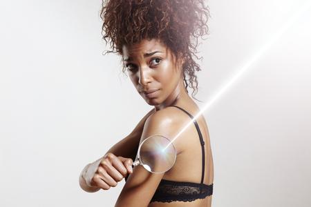 protección: proteccion solar. Mujer con la lente y rayo de láser para la piel