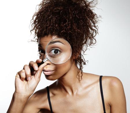 nieuwsgierige vrouw met magnifer lenscloseup menselijk zoeken wit zakelijke vergrootglas vrouwelijke vergrotingslens jonge bedrijf blik gezicht vrouw schoonheid exploratie vergroten onderwijs mooie achtergrond door glas loupe oog