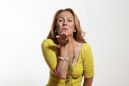 rubia ojos azules: Mujer mayor feliz que envía un beso