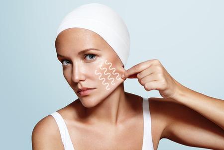 piel: mujer pellizca la piel en su cara con un dedo, líneas en la cara