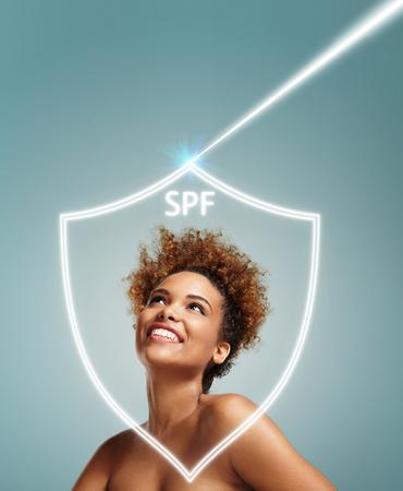 fille noire: Bonne fille noire regardant sur les rayons UV, derri�re le bouclier de SPF. Notion SPF LANG_EVOIMAGES