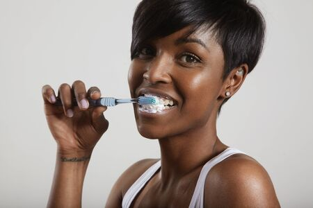 routine: black woman cleaning her teeth LANG_EVOIMAGES