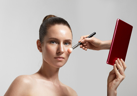 tutorial: woman with a planshet and hand from it is making a makeup Stock Photo
