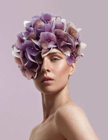 beauty woman watching at camera, wearing hortensia's flowers on the head photo