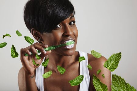 dental floss: woman cleaning her teeth, mint leavs Stock Photo