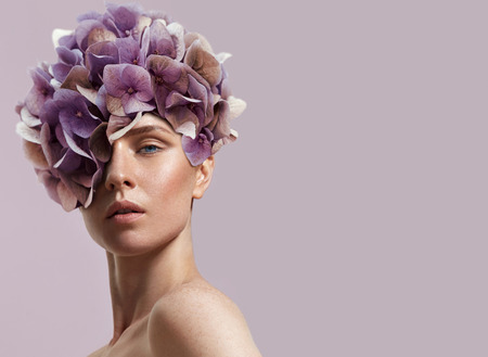 beauty woman watching at camera, not smiling, hortensia's flowers on the head
