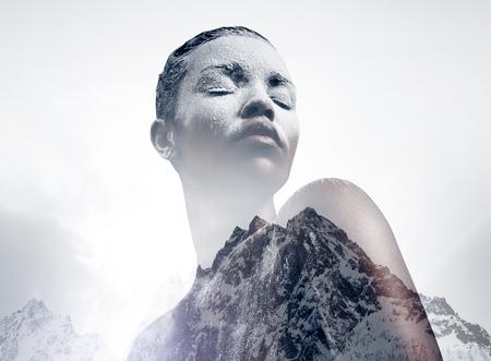 exposicion: mujer de negro cubierto por la doble exposición de polvo blanco con una montaña LANG_EVOIMAGES