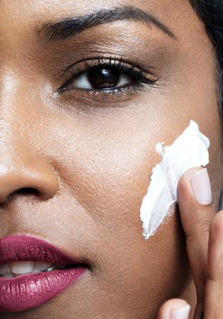cheek to cheek: beauty black woman put cream on a cheek. closeup portrait. Ideal skin